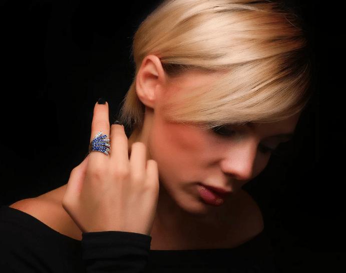 Выбираем цвет сапфира. Девушка блондинка примеряет кольцо с сапфиром
